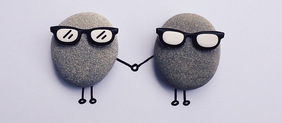 Two rocks with cartoon glasses holding hands